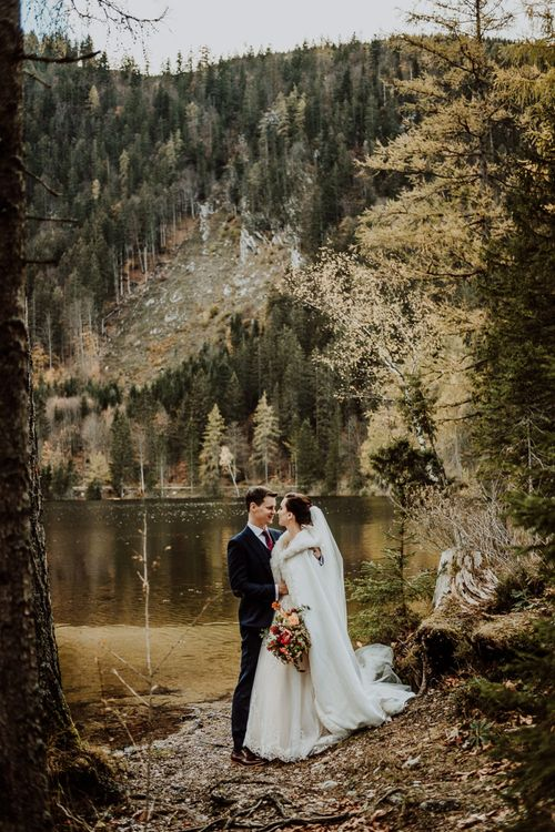 Bride in Long Cover Up Standing With Her Groom by The Waters Edge in Hallstatt, Austria