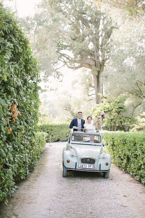 Bride in Rime Arodaky Wedding Dress and Groom in Traditional Morning Suit Travelling in VW Beetle