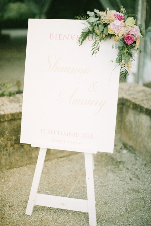 White Wedding Welcome Sign with Gold Lettering and Corner Floral Arrangement