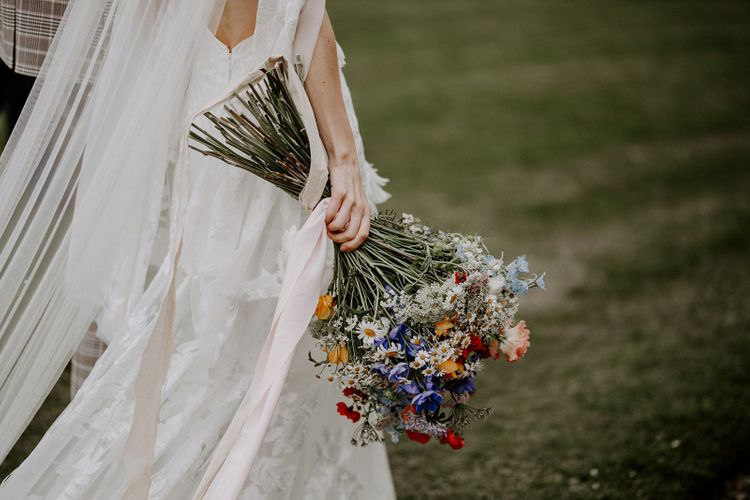 Bride carrying wildflower bouquet for micro wedding