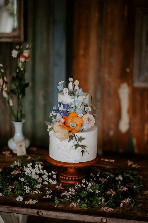 Wedding cake with wooden cake toppers and wildflower decor