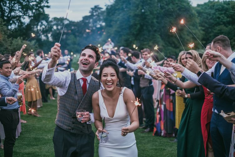 Sparkler Moment with Bride in Pronovias Wedding Dress and Groom in Plaid Waistcoat