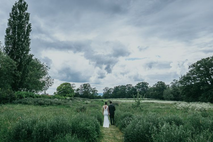 Bride and Groom Walking Through Elmore Court's Gardens