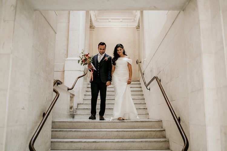 Bride and groom walking down the steps at Town Hall wedding