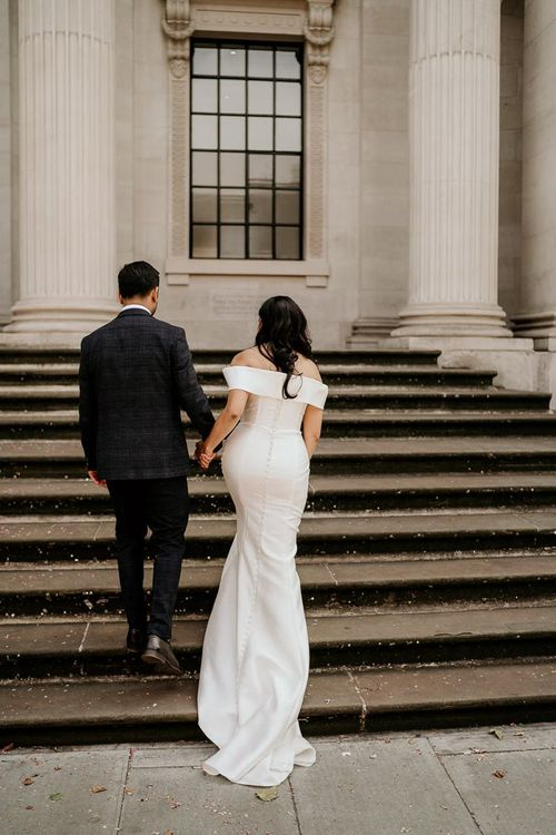 Bride and groom walking up the steps at Old Marylebone Town Hall