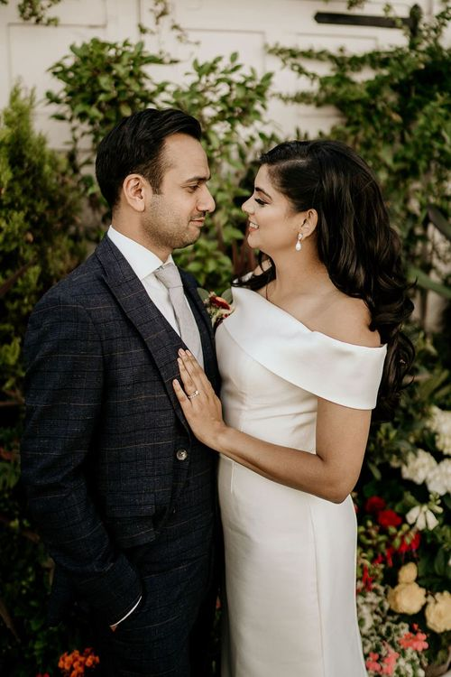 Groom in check suit and bride in off the shoulder wedding dress
