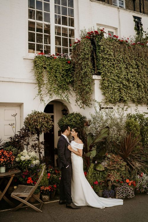 Bride and groom portrait in front of a plant covered building