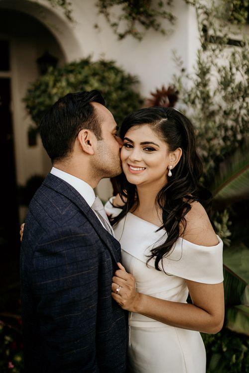 Groom kissing his bride with long wavy hair and natural makeup