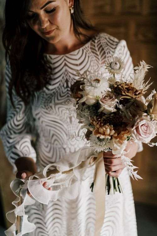 Bride in Margaux Tardits Wedding Dress with Swirl Pattern Holding Her Nude Wedding Bouquet Tied With Ribbon