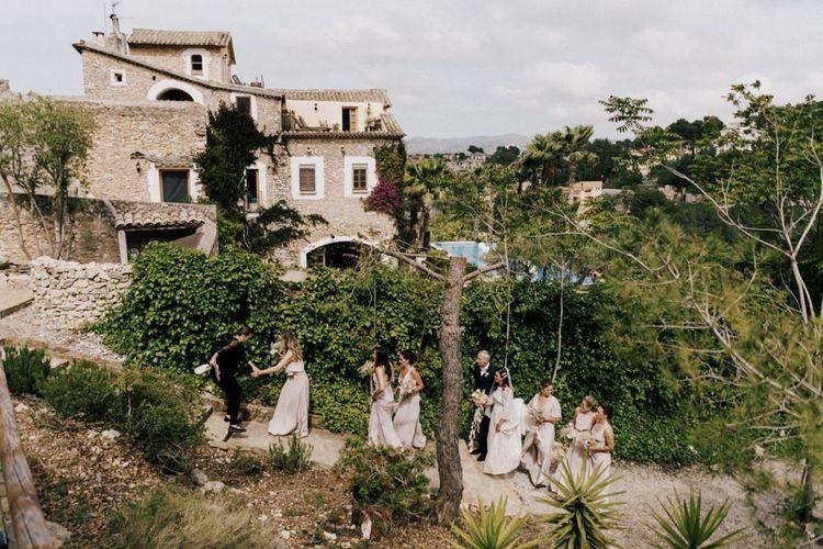 Bridal Party Walking to the Outdoor Wedding Ceremony at Almiral de la Font Barcelona Manor House  Wedding Venue