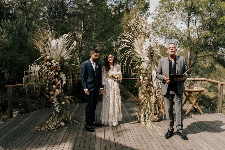 Bride and Groom Standing at the Floral Altar in a Margaux Tardits Wedding Dress and Moss Bros. Navy Wedding Suit