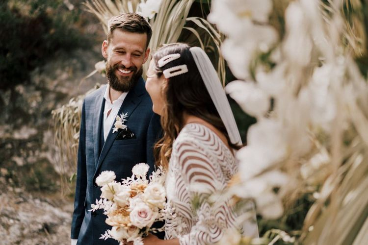 Groom in Moss Bros. Navy Wedding Suit and Bride in Margaux Tardits Wedding Dress Laughing During the Wedding Ceremony