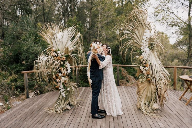 Bride in Margaux Tardits Wedding Dress  and Groom in a Navy Wedding Suit  Kissing at the Altar