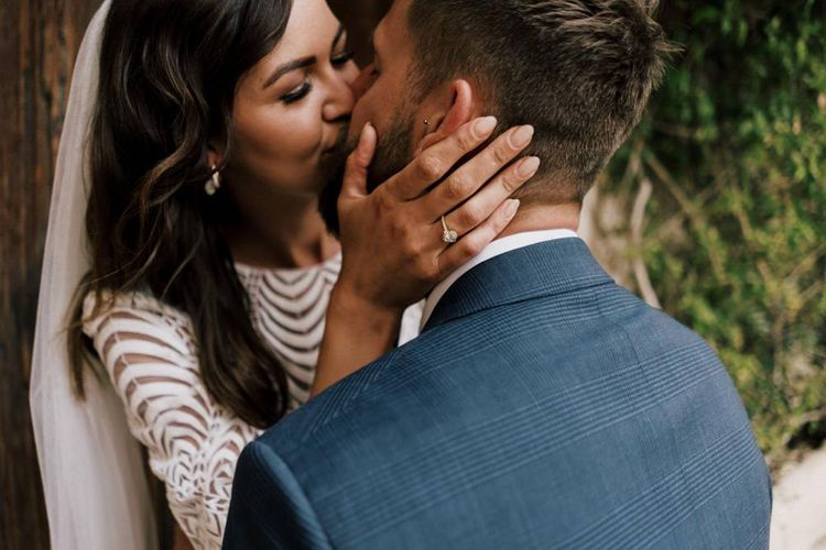 Bride Kissing Her Husband in a Navy Check Moss Bros. Wedding Suit