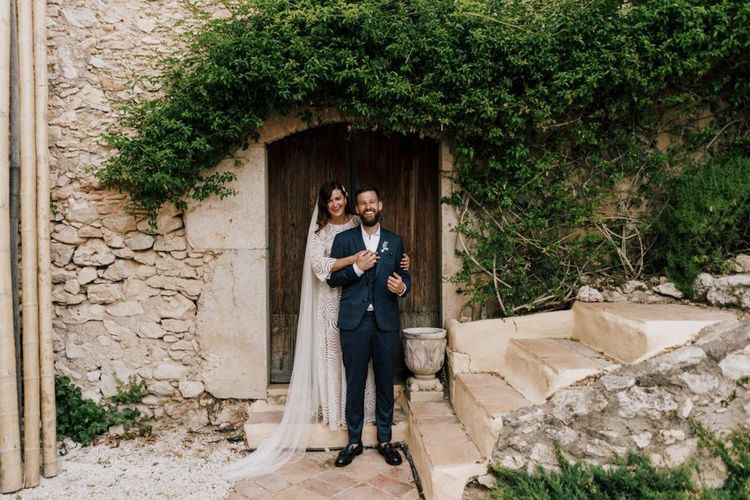 Bride in Margaux Tardits Wedding Dress with Embracing Her Husband in a Moss Bros. Check Wedding Suit