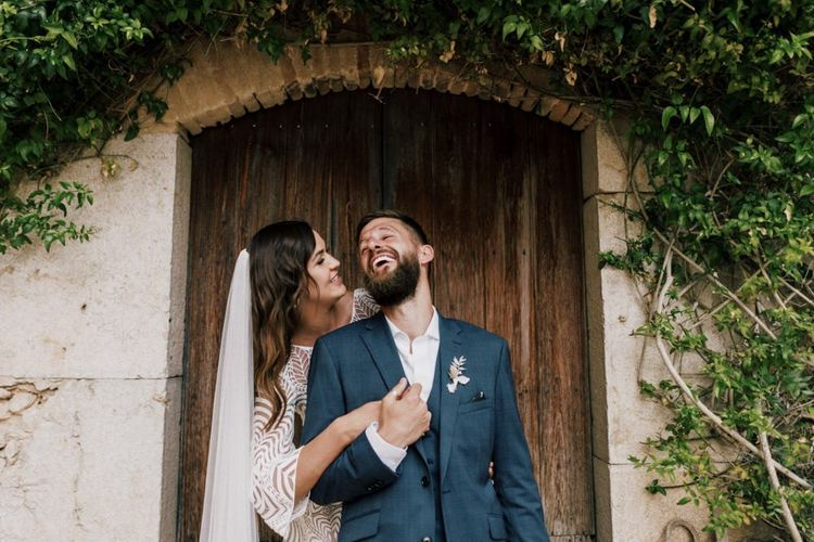 Groom in Navy check Moss Bros. Wedding Suit and Bride in Margaux Tardits Wedding Dress Laughing