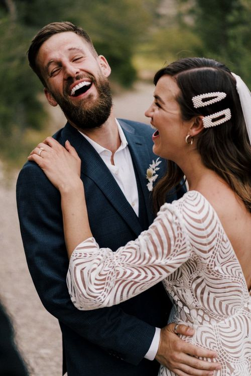 Bearded Groom in White Shirt and Navy Blazer Laughing with His Bride in a Pattern Wedding Dress and Pearl Hair Slides