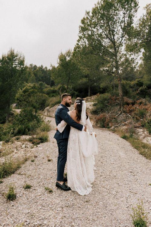 Bride in Margaux Tardits Wedding Dress and Groom in Navy Wedding Suit Embracing