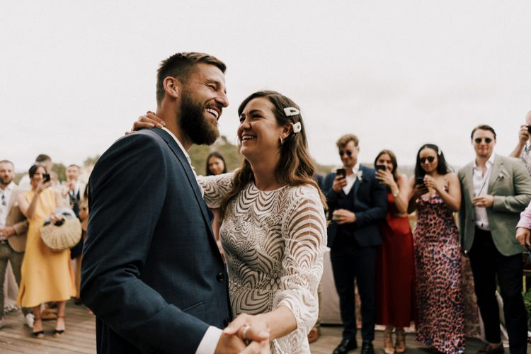 First Dance with Groom in Navy Suit and Bride in Swirl Patterned Wedding Dress