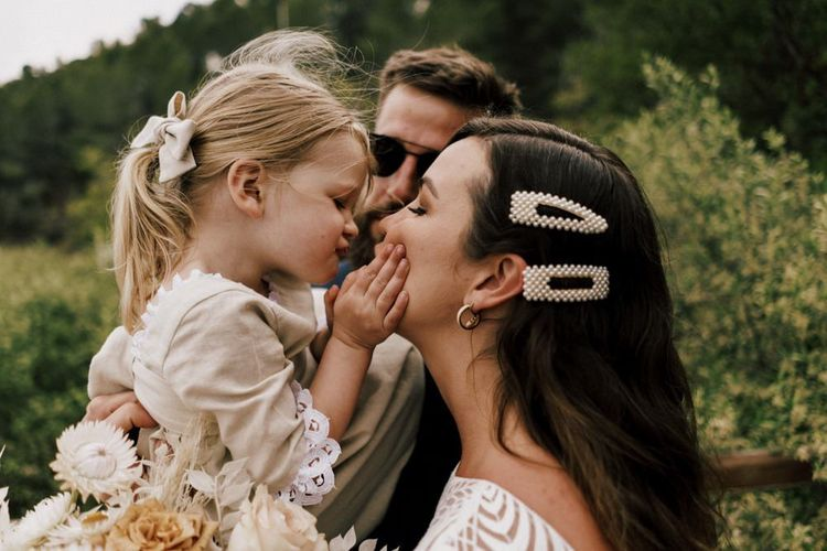 Bride with Pearl Hair Slides and young Daughter Sharing a Kiss