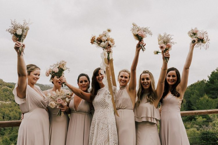 Happy Bridal Party Portrait with Bridesmaids Waving Their Bouquets