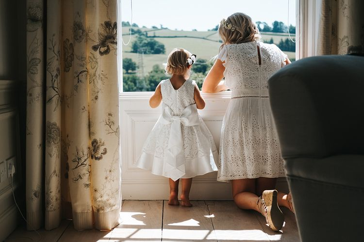 Bridesmaid in White Broderie Anglaise Dress Crouching Down Looking out The Window with a Little Flower Girl