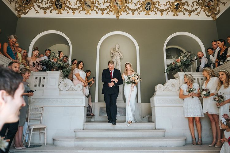 Bride in Fitted Savannah Miller Chloe Wedding Dress and Flower Crown Escorted Down the Aisle by her Father