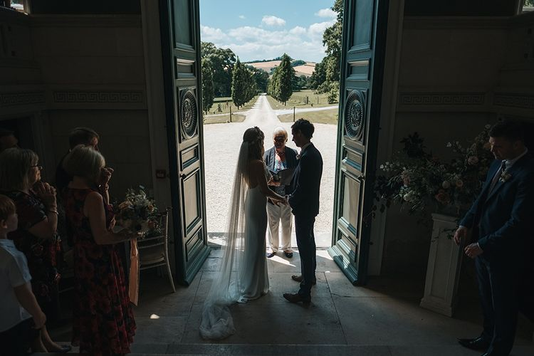 Bride and Groom Taking Their Vows in the Entrance on Pynes House