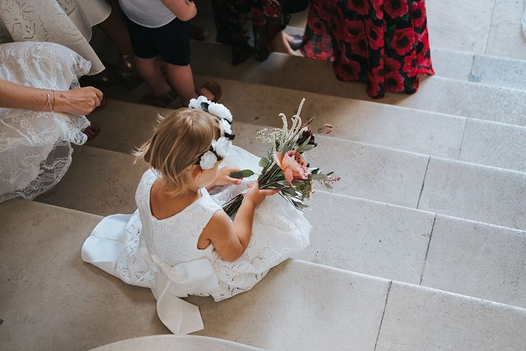 Flower Girl Sitting on The Steps Playing With Her Bouquet