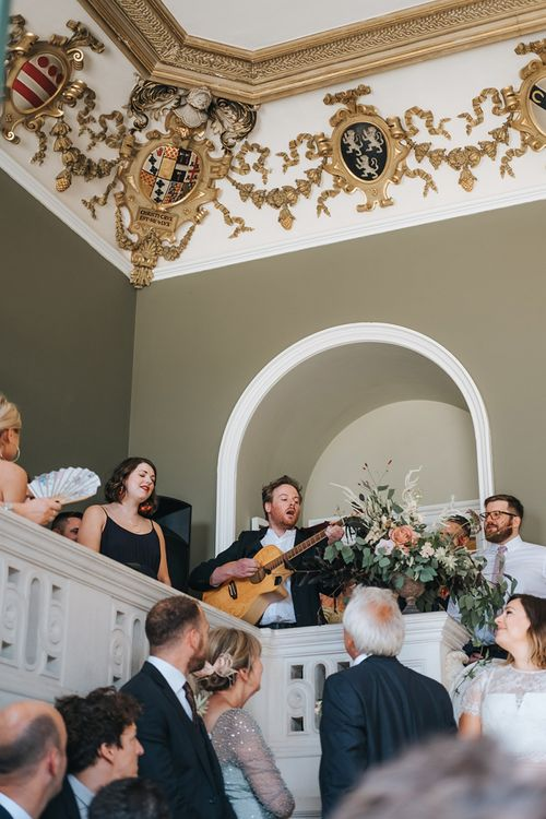 Wedding Guest Playing Guitar During The Wedding Ceremony at Pynes House, Devon