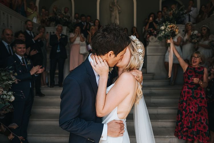 Bride in Slinky Wedding Dress and Groom Kissing During the Wedding Ceremony