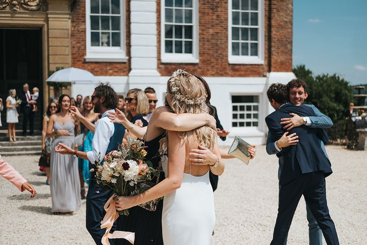 Wedding Guests Embracing the Bride in a Spaghetti Strap Savannah Miller Wedding Dress and Flower Crown