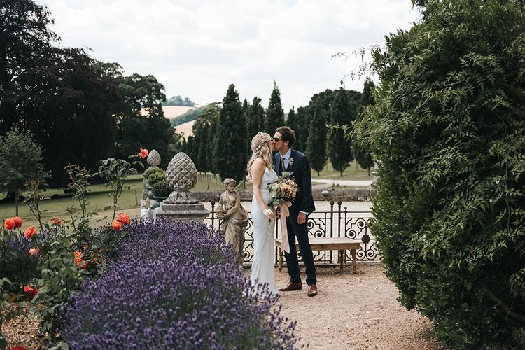 Bride in Fitted Savannah Miller Chloe Wedding Dress and Flower Crown Kissing Her Groom in the Pynes House Gardens