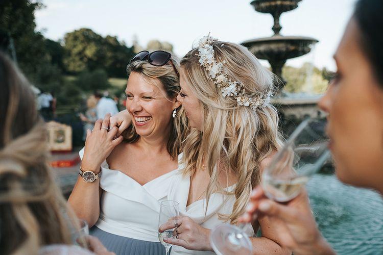 Bride in Flower Crown Hugging Her Wedding Guest