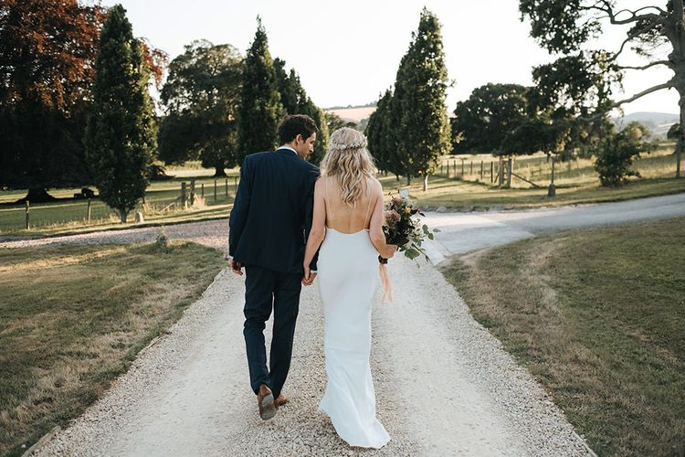 Bride and Groom Walking Down the Country Lane Showing off The Brides Backless Savannah Miller Wedding Dress