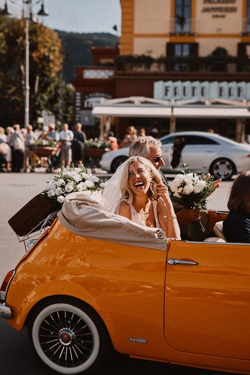 Bride arriving for wedding in a convertible orange fiat 500