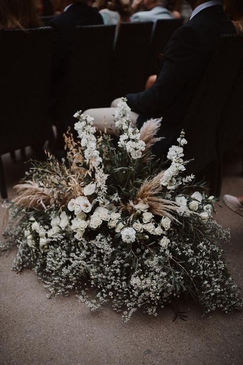 White aisle wedding flowers mixed with foliage and pampas grass