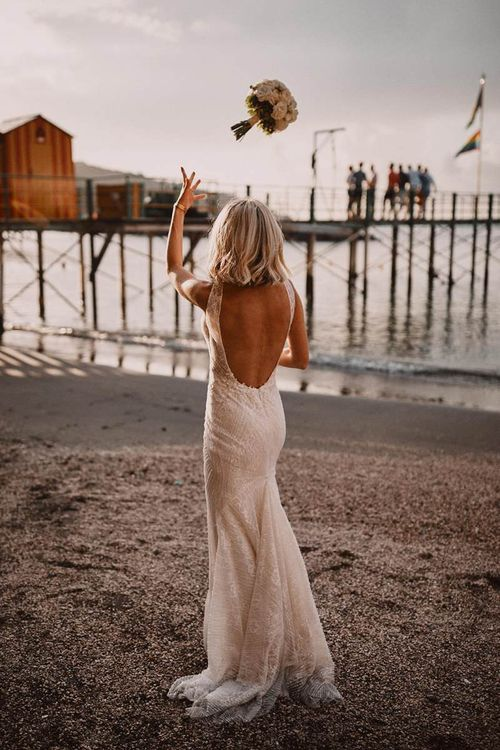 Bride in backless Enzoani wedding dress throwing the wedding bouquet