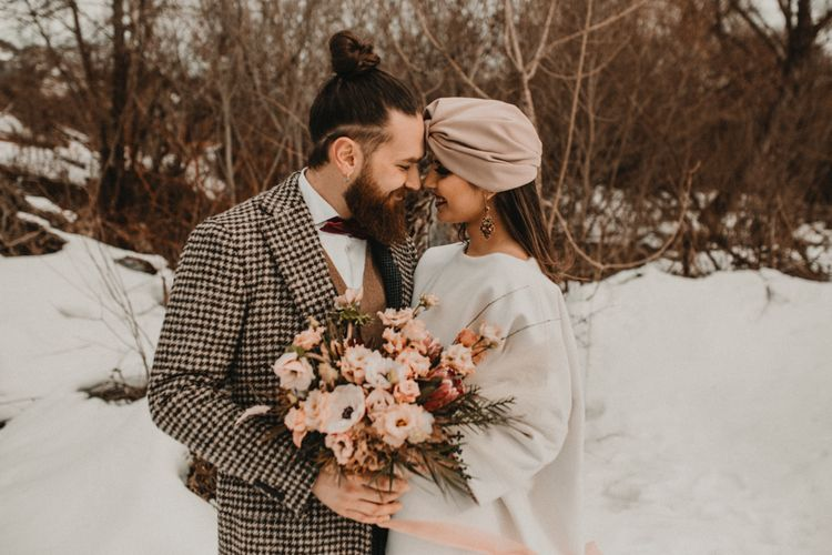Stylish bride and groom at snow wedding with peach wedding bouquet