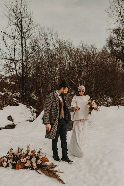 Bride and groom holding hands at snow Italian mountains elopement