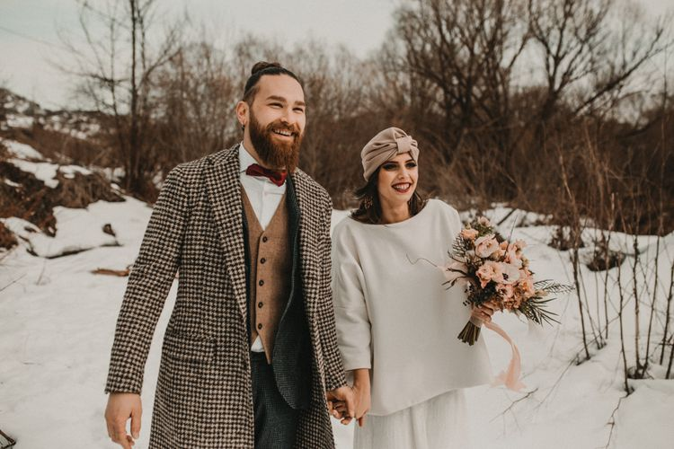 Groom in wool waistcoat and overcoat and bride in jumper and turban  at snow wedding