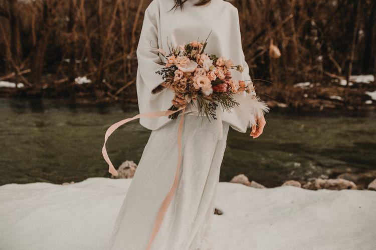 Bride holding a peach wedding bouquet tied with ribbons