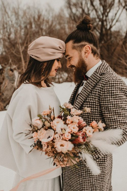 Intimate wedding portrait of bride and groom at snow wedding