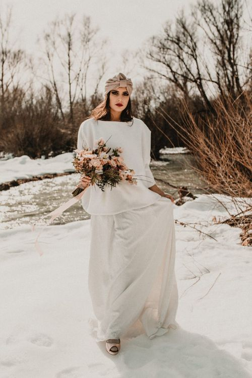 Bride in wedding dress, jumper and turban for snow wedding