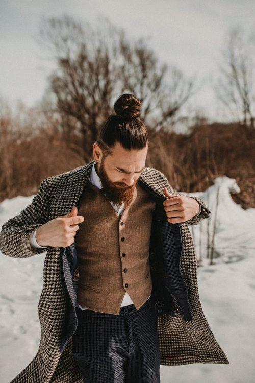 Stylish groom with waistcoat, topknot and beard