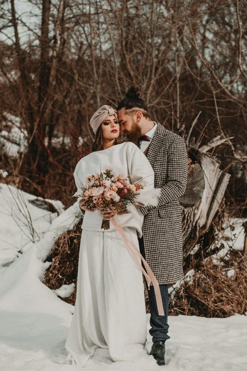 Stylish bride and groom embracing at snow wedding