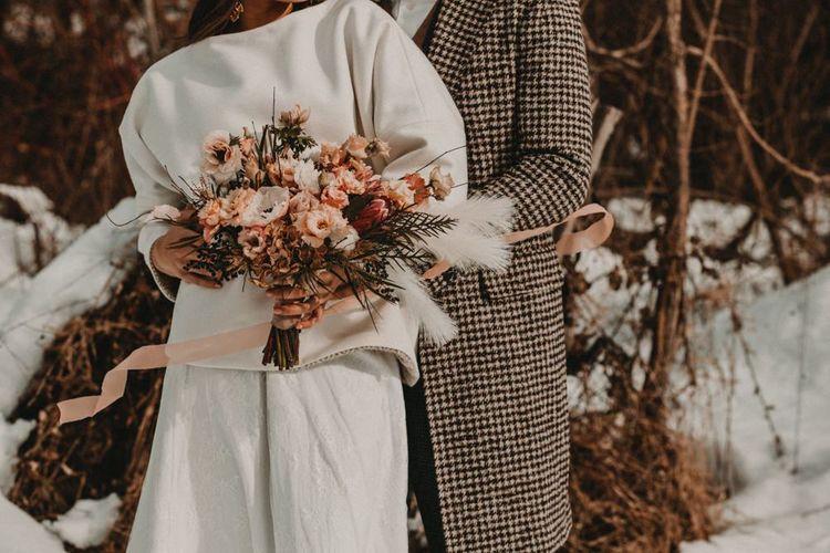 Bride in jumper and groom in overcoat for Winter wedding