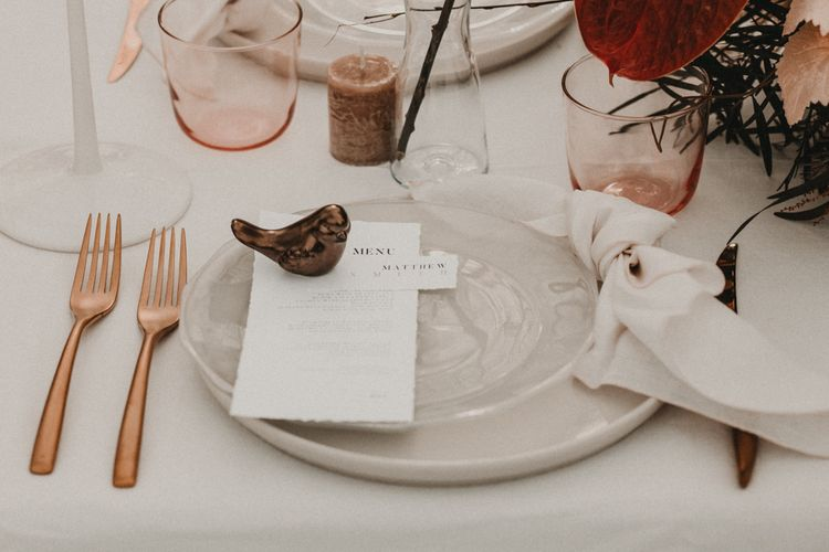 Elegant place setting with rose gold cutlery and ceramic bird decor