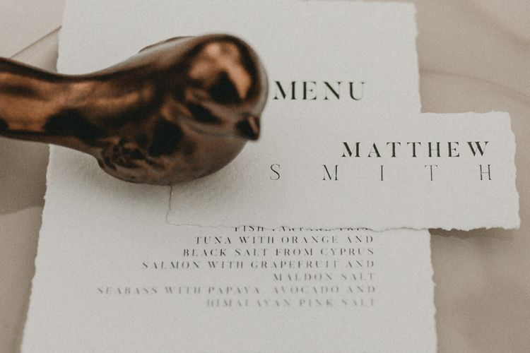 Ceramic bird on top of menu and place setting cards