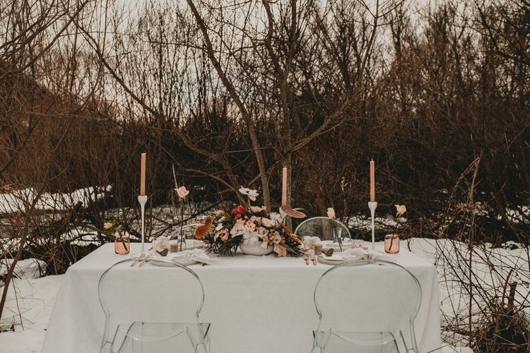 table scape at Italian elopement  with ghost chairs and romantic flower centrepiece